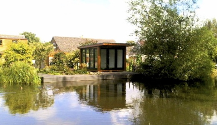 Garden room overlooking a canal with swans passing by